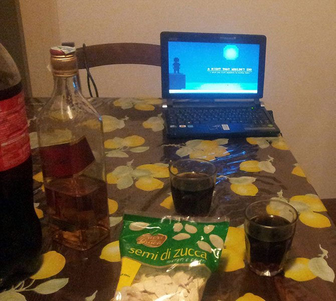 Photo of kitchen table with drinks and laptop with loaded screenshot of released game.