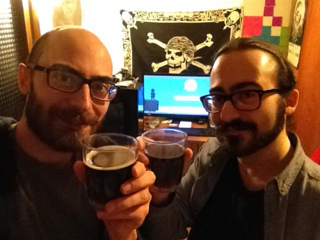 Photo of Leafdog Games Brothers while drinking to celebrate the release of the game, with screen behind showing the game intro